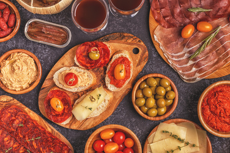 Typical spanish tapas concept. Concept include slices jamon, chorizo, sausage, bowls with olives, tomatoes, anchovies,  mashed chickpeas, cheese. Foto de archivo - 95350448