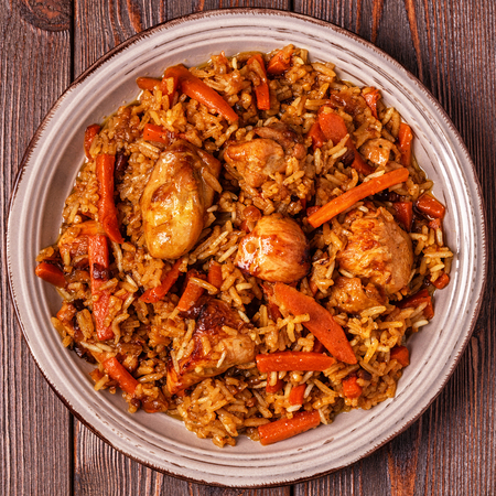Pilaf (biryani) on a wooden background, top view, copy space.