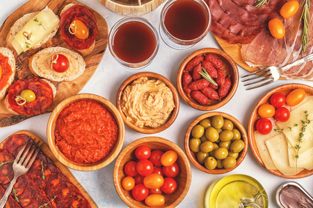 Typical spanish tapas concept. Concept include slices jamon, chorizo, sausage, bowls with olives, tomatoes, anchovies,  mashed chickpeas, cheese. Фото со стока