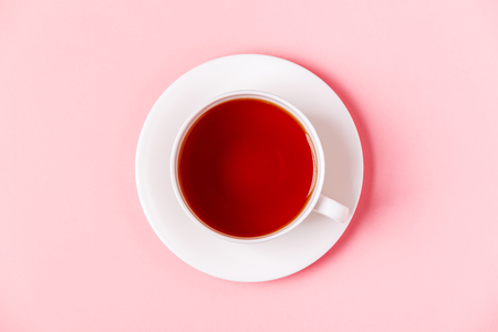 Cup of tea on a pink pastel background, top view.