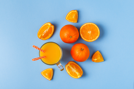 Oranges and juice on a blue pastel background, top view.