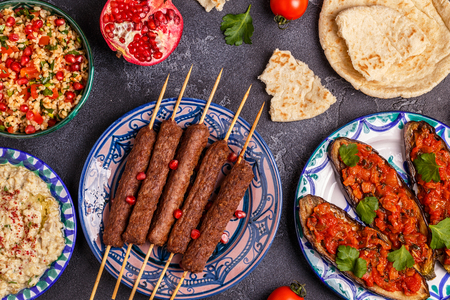 Classic kebabs, tabbouleh salad, baba ganush and baked eggplant with sauce. Traditional middle eastern or arab dish. Top view.