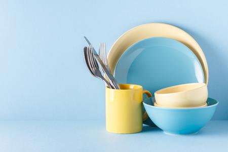 Naczynia i sztućce na niebieskim tle pastelowych z miejsca na kopię.