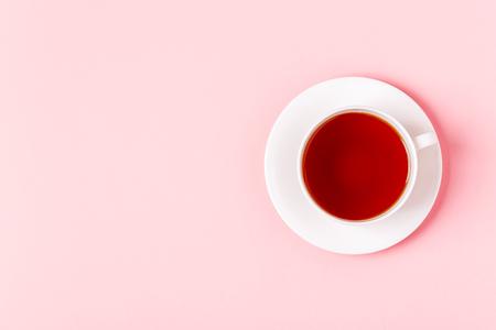 ピンクのパステルの背景にお茶のカップ、トップビュー。 写真素材
