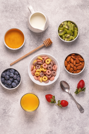 Breakfast with colorful cereal rings, fruit, milk, juice. Top view.