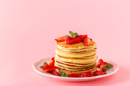 Pancakes with berries on a bright pastel background, copy space. Stockfoto