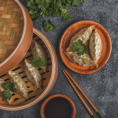 Fresh dumplings on a dark stone background. Asian cuisine, top view, copy space. Stock Photo