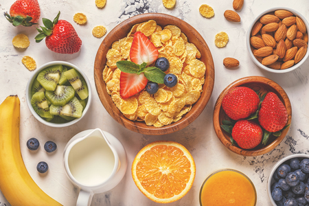 Healthy breakfast - bowl of corn flakes, berries and fruit, nuts, orange juice, milk, top view.