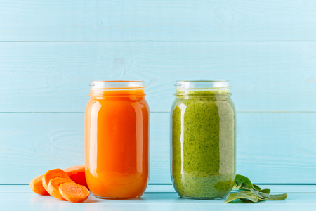Orange/green colored smoothies / juice in a jar on a blue background. Archivio Fotografico