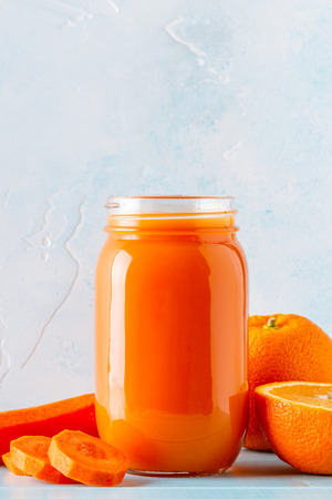 Orange-colored smoothies  juice in a jar on a blue background. 版權商用圖片