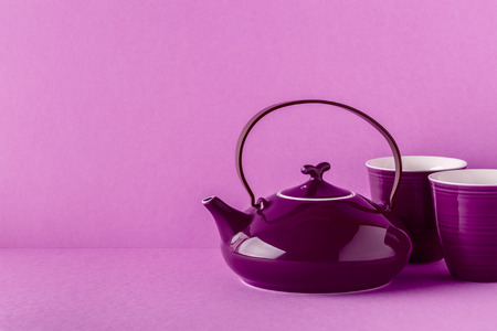 Purple teapot and cups on a lilac background with copy space. Zdjęcie Seryjne