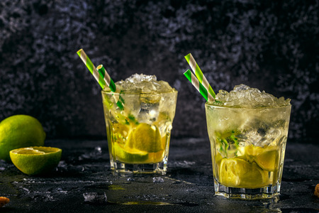 Fresh lime cocktail with ice on dark background.