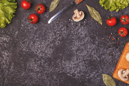 Ingredients for cooking on dark concrete background, top view, copy space.