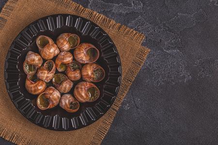 Fried snails with lemon, baguette and parsley, top view. Banque d'images
