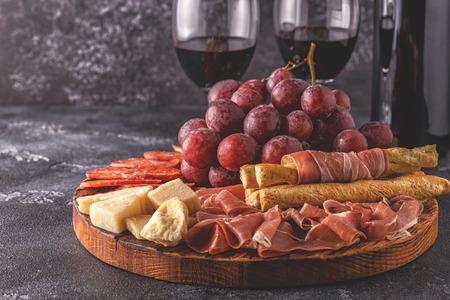 Prosciutto, saucisse, vin, raisin, parmesan sur tableau noir, mise au point sélective. Banque d'images