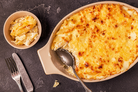 Mac and cheese, american style macaroni pasta in cheesy sauce, top view.