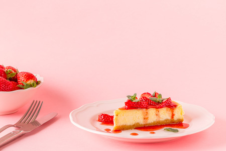 Delicious homemade cheesecake with strawberries on pink background.