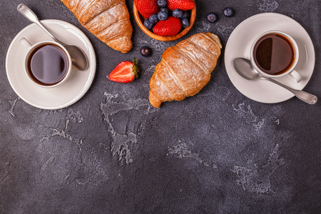Breakfast with fresh croissants, orange juice and coffee, top view.