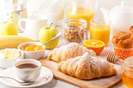 Desayuno continental con croissants recién hechos, jugo de naranja y café, enfoque selectivo.