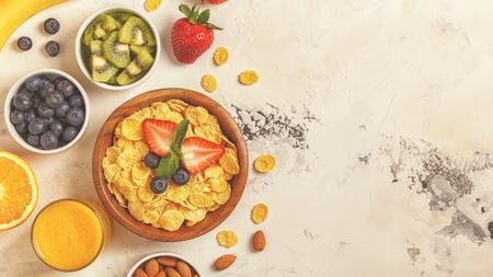 Healthy breakfast - bowl of corn flakes, berries and fruit, nuts, orange juice, milk, top view.
