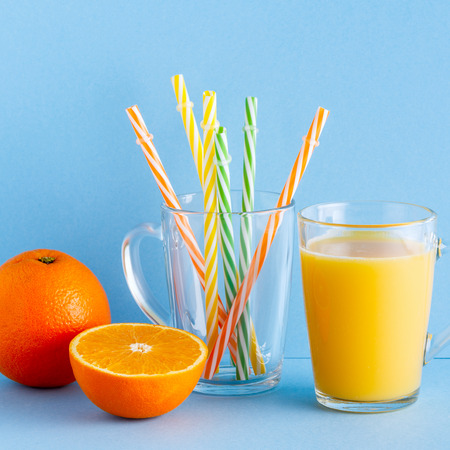 Orange juice on a blue pastel background with copy space.