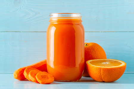 Orange-colored smoothies / juice in a jar on a blue background. Standard-Bild