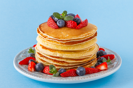 Pancakes with berries on a bright pastel background, copy space. Reklamní fotografie