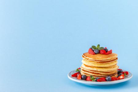 Panqueques con frutos rojos sobre un fondo pastel brillante, copie el espacio.