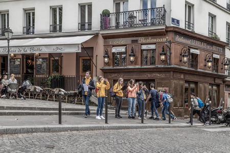 Young people take pictures of the sights in Paris in the Montmartre district. April 2018, Paris, France.