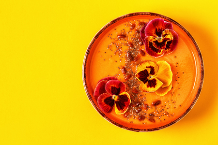 Smoothie bowl with edible pansy flowers, chia seeds, goji berries, top view. Stock Photo