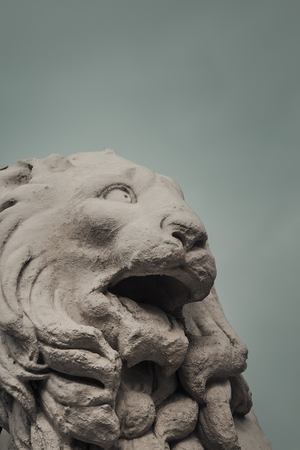 Marble lion head  against a cloudy sky background. Stock Photo