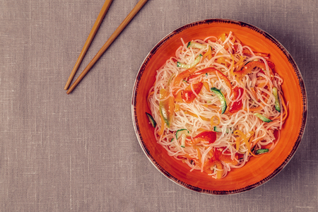 Glass noodle salad with cucumber pepper and carrot on a linen tablecloth, top view