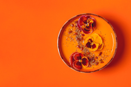 Smoothie bowl with edible pansy flowers, chia seeds, goji berries, top view. Archivio Fotografico