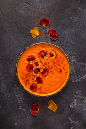 Smoothie or pumpkin  carrot soup with saffron and edible petals pansy flowers, top view. Stock Photo