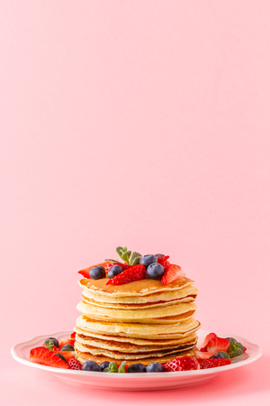 Pancakes with berries on a bright pastel background, copy space. Stock Photo