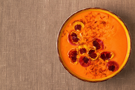 Smoothie or pumpkin  carrot soup with saffron and edible petals pansy flowers, top view. 版權商用圖片