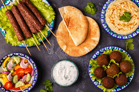 Classic kebabs, falafel and hummus on the plates. Top view.