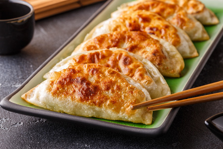 Plate of asian gyoza, dumplings snack with soy sauce. Stock Photo