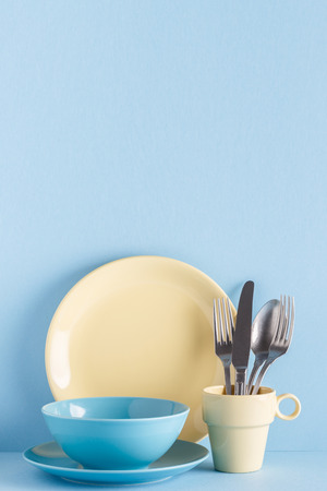 Crockery and cutlery on a blue pastel background with copy space. Standard-Bild - 104062926