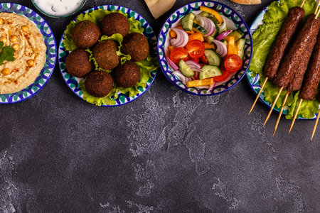 Classic kebabs, falafel and hummus on the plates. Top view, copy space. Stock Photo