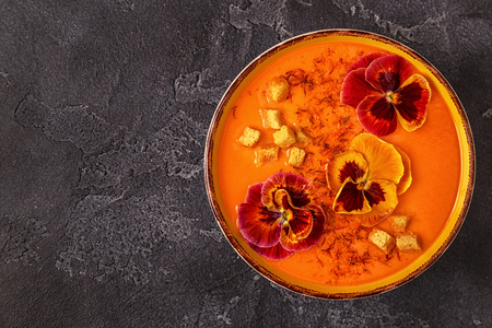 Pumpkin  carrot soup with saffron and edible flowers pansy, top view.
