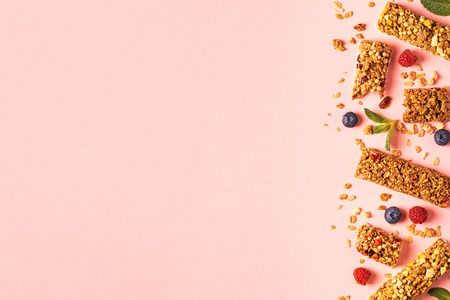 Cereal bars on a bright pastel background, top view. Reklamní fotografie