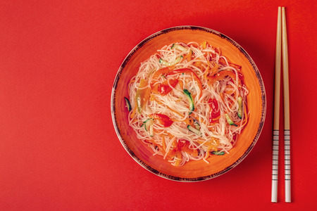 Glass noodle salad with cucumber pepper and carrot on a bright pastel background, top view.