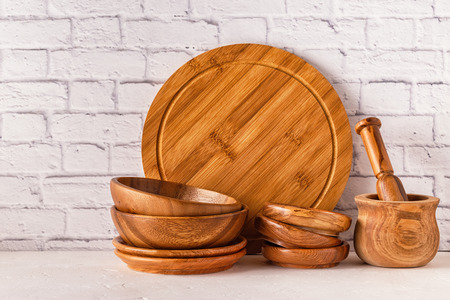 Wooden tableware on a white table with copy space.