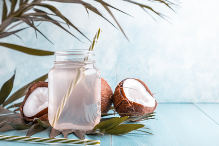 Coconut water and coconuts on a bright pastel background, selective focus.