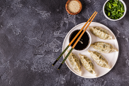Asian dumplings, soy sauce, chopsticks. Top view, copy space. Stock Photo - 106564304