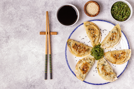 Gyoza or dumplings snack with soy sauce, top view.