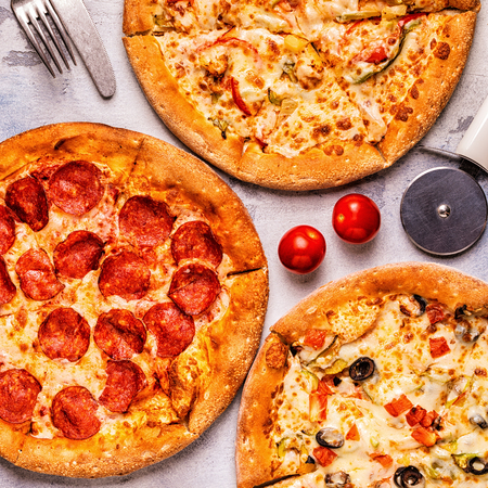 Set of different pizzas - pepperoni, vegetarian, chicken with vegetables, top view Banco de Imagens