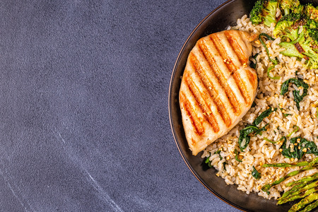 Grilled chicken breast with brown rice, spinach, broccoli, asparagus, concept of diet, healthy eating.