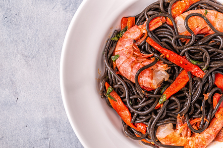 Black spaghetti with prawns and vegetables, top view.